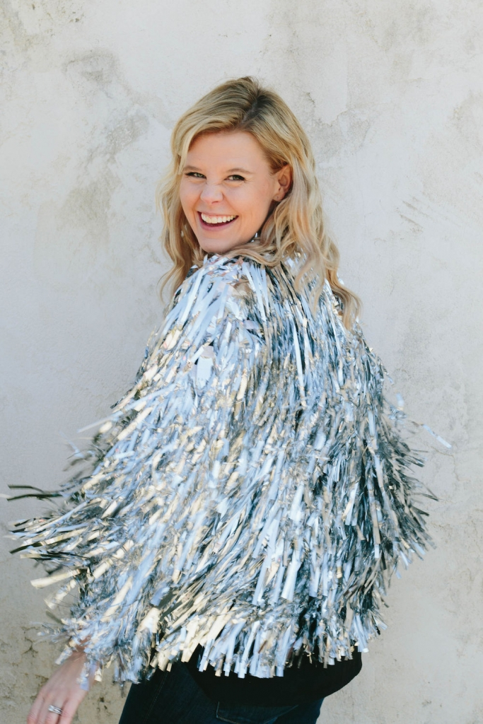 Christina laughing and twirling in her silver tinsel jacket