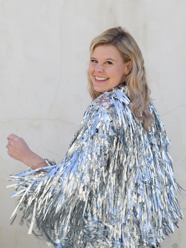 Christina wearing a silver tinsel jacket and looking over her shoulder