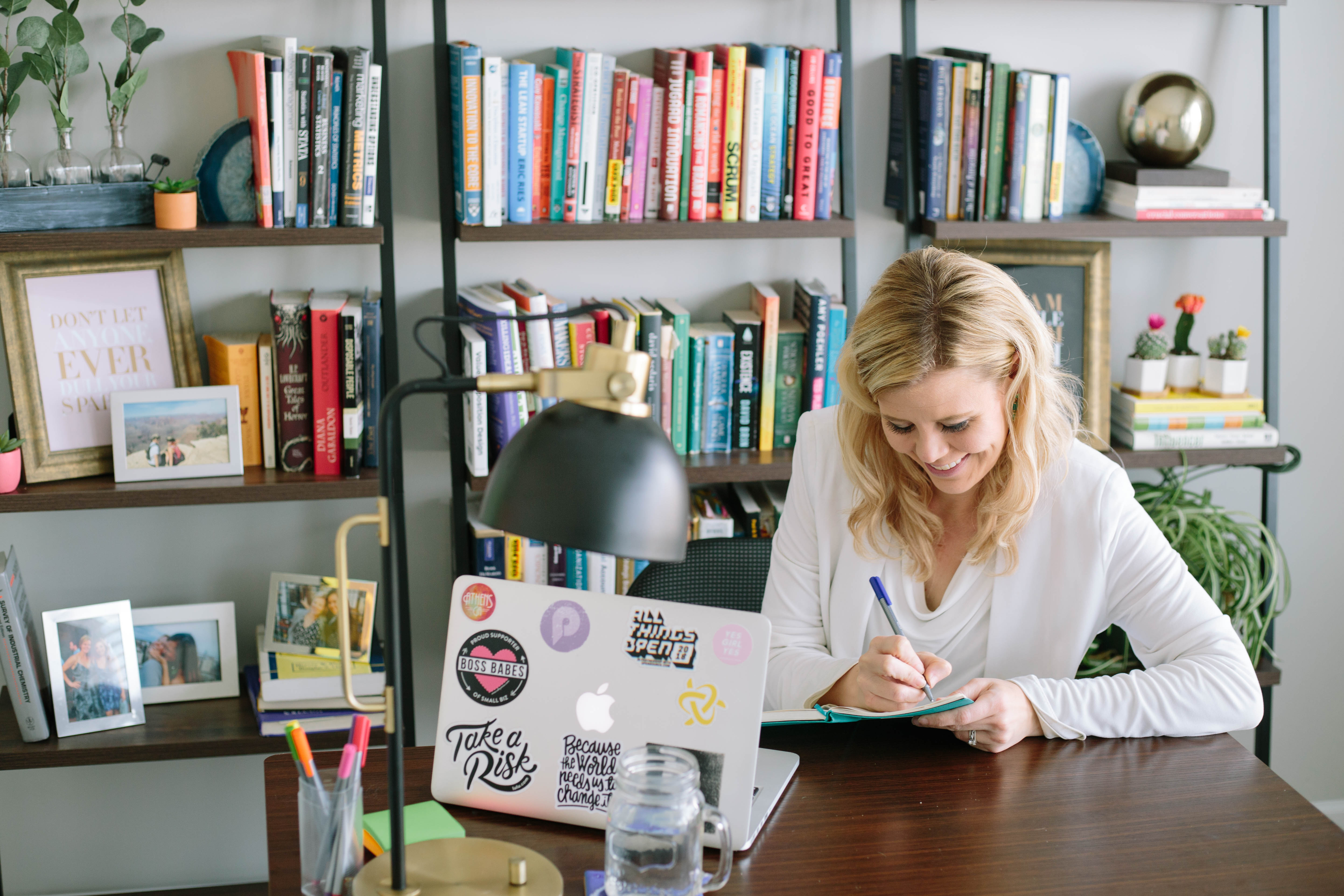 blond haired woman at desk taking notes with bookshelf behind her