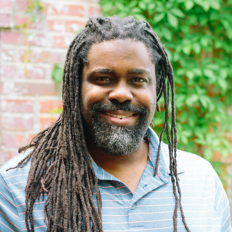 Geraud Staton, a brilliant black man with dreadlocks and a beard smiling