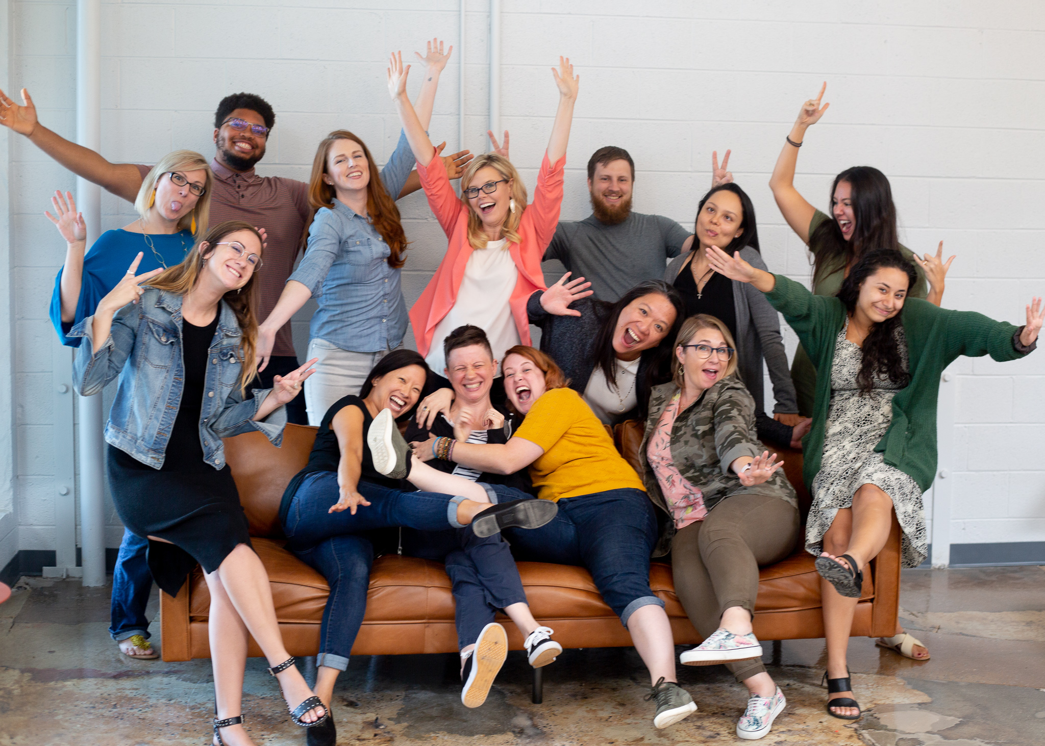 Group of women entrepreneurs being goofy and happy, along with a handful of male advisors that are allies