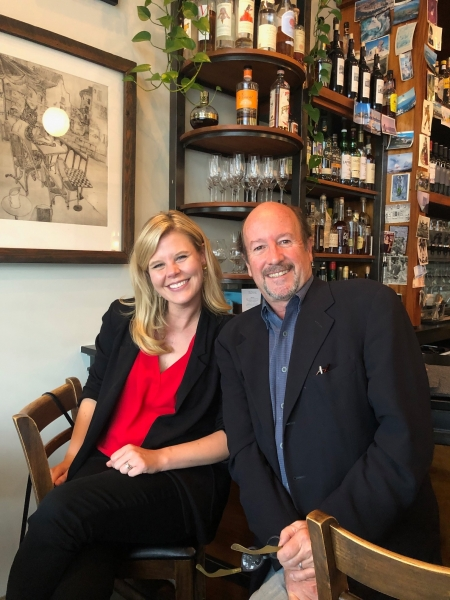 Christina sitting in front of a bar with her professor, David Sutherland