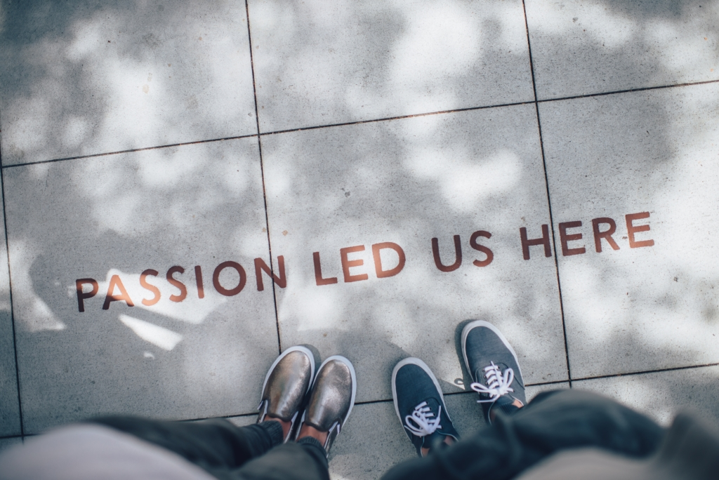 """Photo of two people's feet on a sidewalk that says """"Passion led us here"""""""