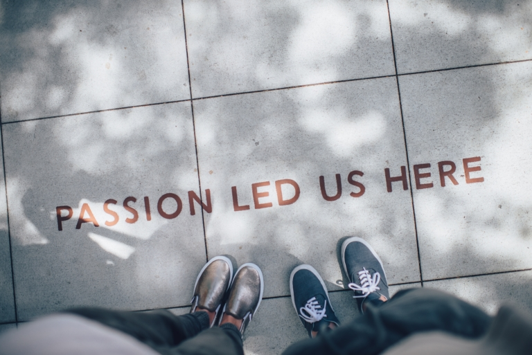 "Photo of two people's feet on a sidewalk that says ""Passion led us here"""