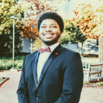 Jalen, a black, college-aged young man in bow tie & suit smiling on campus